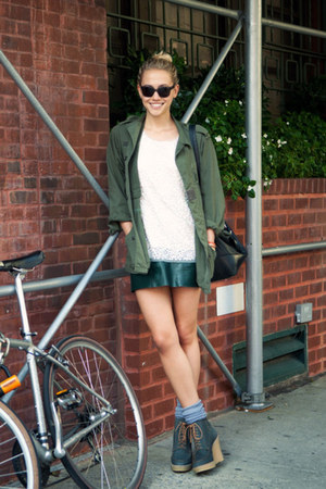 green coat - ankle boots - white top - black leather skirt