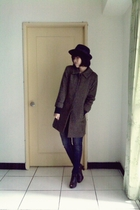 black sweater - green coat - blue jeans - gray shoes - black hat